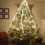 Christmas_Tree_Decorated_With_Silver_Mesh_Ribbon_And_Bulbs_Placed_On_Metal_Pot_In_White_Living_Room_of_Glowing_Decorative_Christ